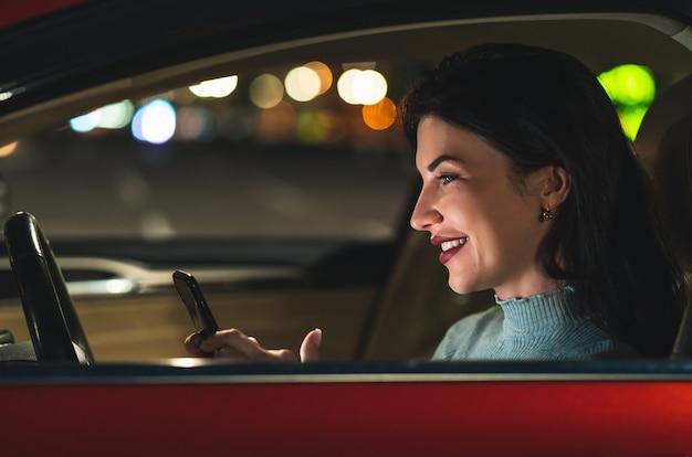 La bella donna con lo smartphone seduta in macchina