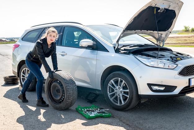 Bella donna con ruota di scorta e auto rotta
