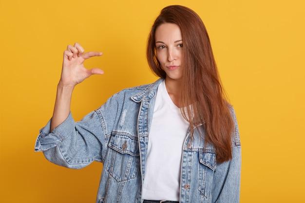Bella donna con la camicia di jeans da portare dei capelli scuri del straighet e la camicia bianca casuale che propone sopra la parete gialla isolata