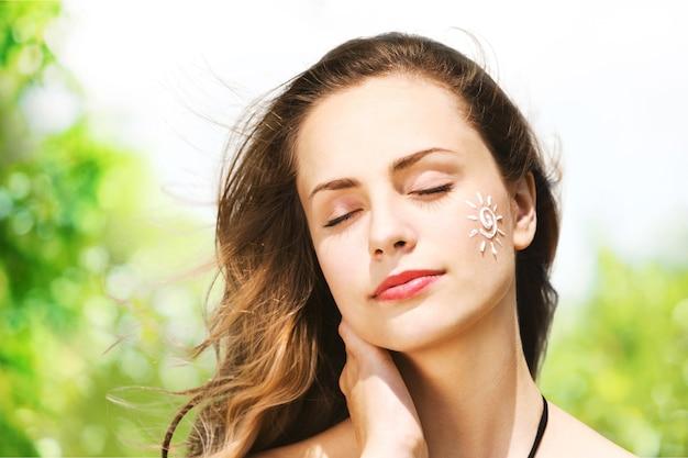 Bella donna con crema solare di protezione solare sopra priorità bassa. abbronzandosi. cura e protezione della pelle.