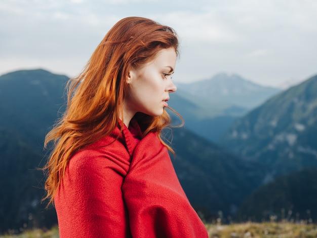 Bella donna con calda coperta in montagna e modello di capelli rossi. foto di alta qualità