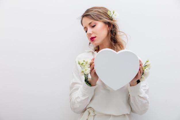 Bella donna con rose bianche che si vestono in una camicia bianca che tiene una confezione regalo a forma di cuore. concetto di primavera o vacanza di san valentino