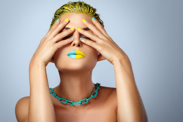 Bella donna con i capelli gialli e unghie e labbra colorate
