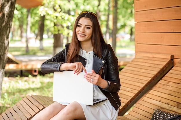 Bella donna che lavora o comunica sul suo laptop bianco, trascorrendo del tempo all'aperto in primavera o in estate.
