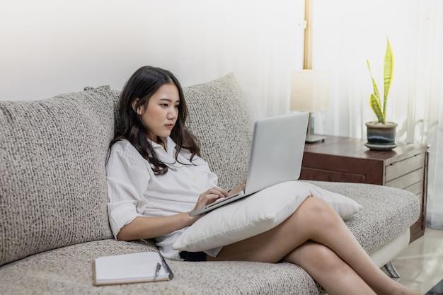 Una bella donna che lavora a casa con un computer portatile e tablet.