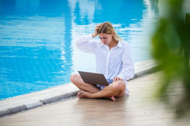 Bella donna che lavora con il computer portatile in piscina. lavoro a distanza freelance