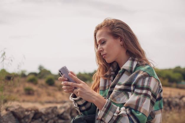 Una bella donna scrive con il suo telefono in mezzo a un sentiero