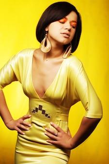 Bella donna in abito giallo su sfondo giallo