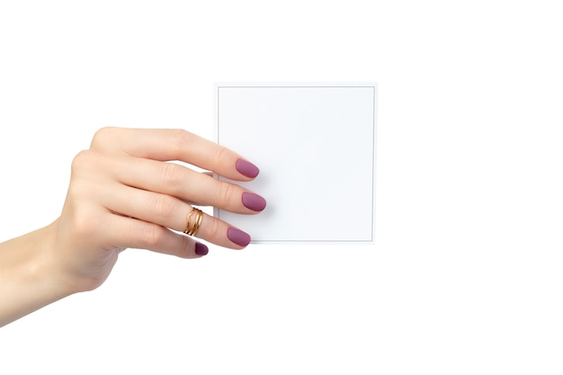 La mano della bella donna con la cartolina della tenuta del manicure isolata