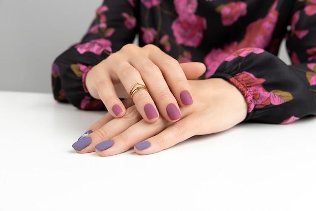 Mani di bella donna con manicure opaca bordeaux viola.