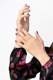 Mani di bella donna con manicure viola bordeaux opaco