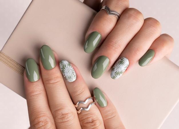 Le mani della bella donna con un design floreale per unghie primavera estate