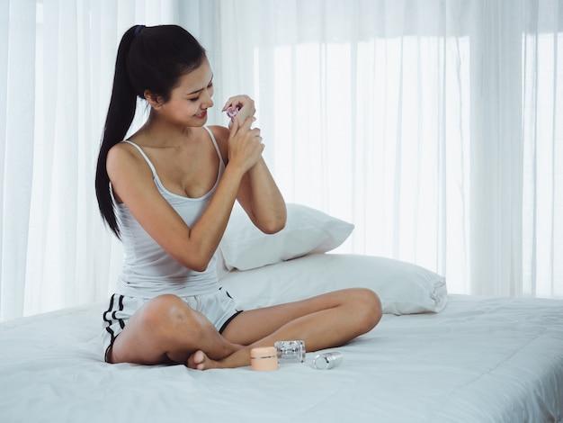 Le belle donne stanno applicando la crema sulle loro braccia