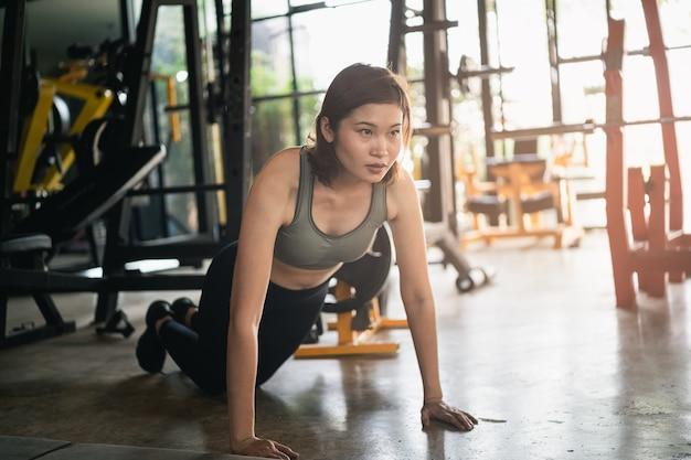 Le belle donne esercitano spingere verso l'alto in palestra, concetto di fitness sport