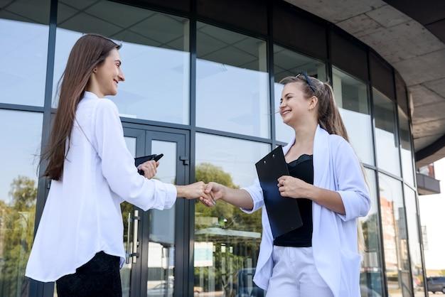 Belle donne che si stringono la mano vicino all'ingresso nell'edificio per uffici Foto Premium