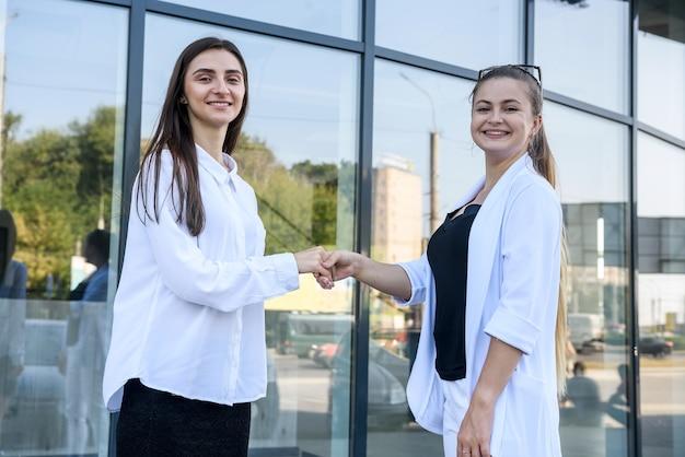 Handshaking di belle donne vicino all'ingresso nell'edificio per uffici