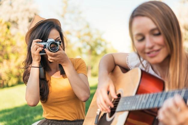 Belle donne che si divertono a suonare la chitarra e la macchina fotografica nel parco. amici e concetto di estate.