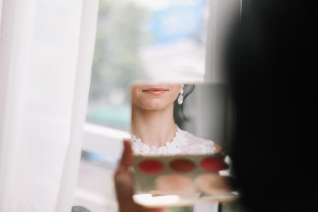 Labbra di belle donne in una mattina nuziale allo specchio