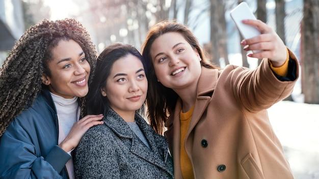 Belle donne in posa insieme durante l'assunzione di selfie