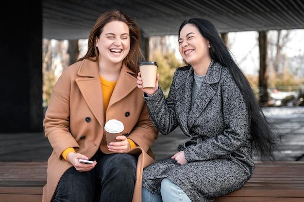 Belle donne in posa insieme alla tazza di caffè