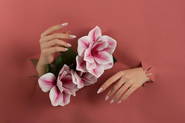 Mani di belle donne con elegante manicure vicino a gigli