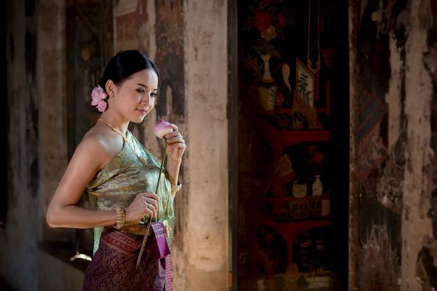 Loto tailandese della mano della tenuta della ragazza delle belle donne in costume tailandese tradizionale con il tempio ayutthaya.