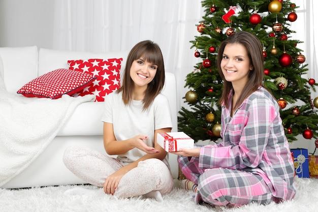 Belle donne gemelle in pigiama vicino all'albero di natale a casa