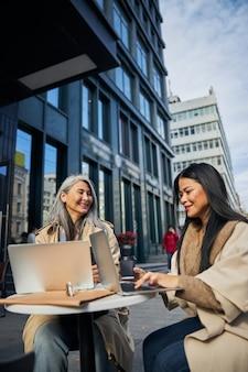 Belle donne che usano computer portatili in un caffè all'aperto
