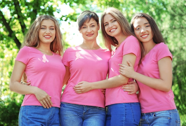 Belle donne che indossano magliette con nastri rosa, all'aperto