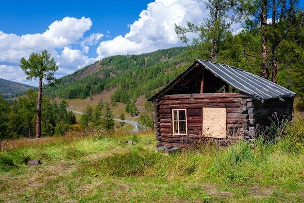 Bella casa di tronchi abbandonata in legno su sfondo di montagne
