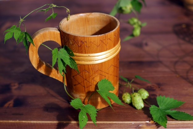 Bellissimo boccale di birra in legno sul tavolo con pianta di luppolo.