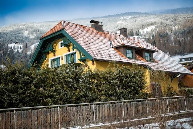 Bella casa in legno nelle alpi contro le alte montagne