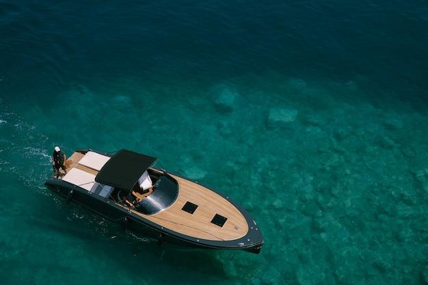 Bellissima barca a motore sportiva in legno con tendalino nero galleggia lentamente sulle limpide acque azzurre del