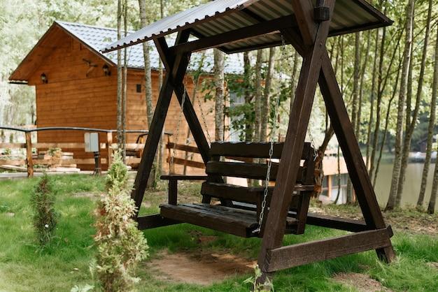 Bella altalena in legno nel giardino sul retro della casa. vista di una casa di campagna in legno nella foresta in una giornata di sole estivo. tranquilla scena rurale.