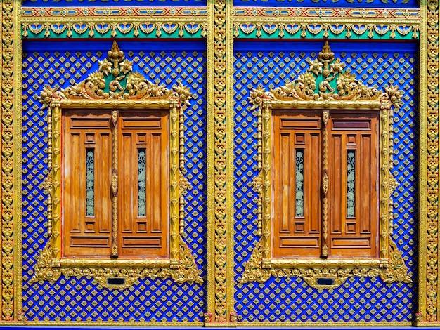 Belle finestre di legno e fondo della parete dello stucco di arte tailandese. stile tailandese del motivo a stucco in bassorilievo nel tempio.