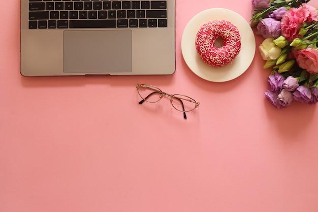 Bellissimo posto di lavoro con laptop, occhiali, ciambella e fiori