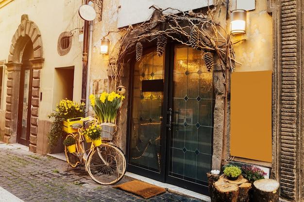 Bei tulipani gialli nel cestino della bicicletta sulla strada vicino al caffè.