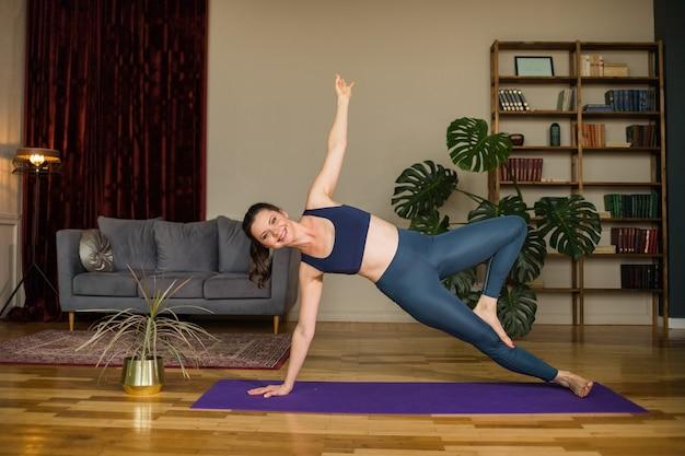 Bella donna di yoga in una tuta da ginnastica esegue asana in una stanza a casa