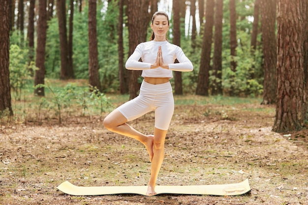 Bella giovane femmina adulta con coda di cavallo che indossa top bianco e leggins in piedi su karemat nella posa dell'albero, fare yoga da solo nella foresta, godersi la natura e l'aria fresca.