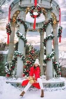 Bella giovane ragazza adulta allegra e felice in un bellissimo gazebo con decorazioni natalizie