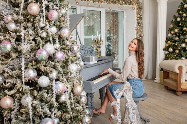 Bella giovane ragazza adulta allegra e felice al pianoforte nella stanza con interni natalizi