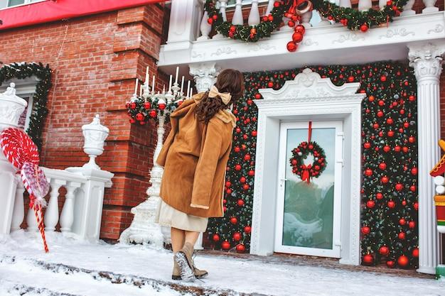 Bella giovane ragazza adulta allegra e felice sotto il portico della casa vicino alla porta a natale