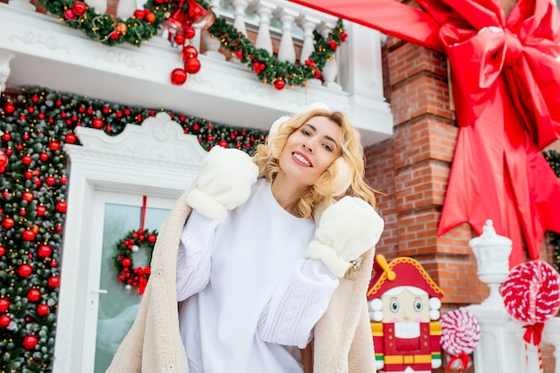 Bella giovane ragazza adulta allegra e felice sotto il portico della casa nelle decorazioni natalizie