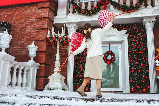 Bella giovane ragazza adulta sotto il portico della casa con lecca-lecca in decorazioni natalizie