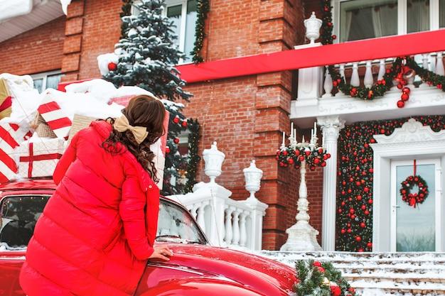 Bella giovane ragazza adulta all'auto rossa sullo sfondo della casa a natale
