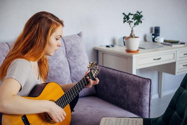 Bella giovane ragazza adulta con i capelli lunghi che suona la chitarra, seduta a casa sul divano, messa a fuoco selettiva. la donna seria pizzica le corde, studiando la melodia. tempo libero domestico, hobby, sviluppo personale.