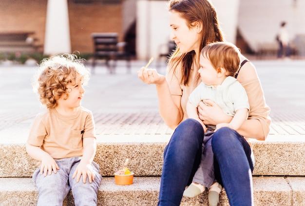Bella giovane madre adulta con i suoi bambini di tre e un anno per strada in estate a mangiare il gelato per andare. concetto di vacanza. programmi estivi all'aperto