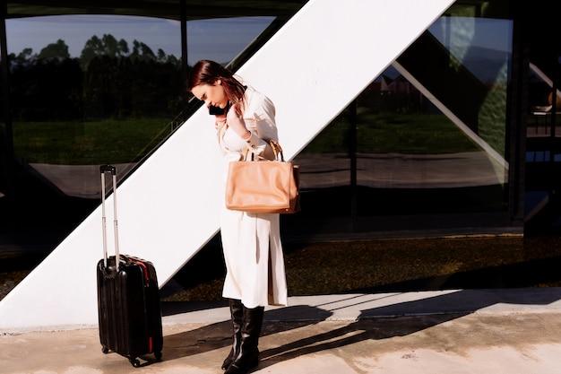 Bella giovane donna adulta in viaggio d'affari che chiama un trasporto nell'area dell'ufficio sulla strada