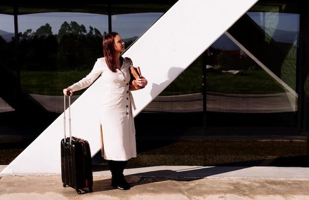 Bella giovane donna adulta in viaggio d'affari in attesa di trasporto guardandosi intorno nervosamente nell'area dell'ufficio sulla strada