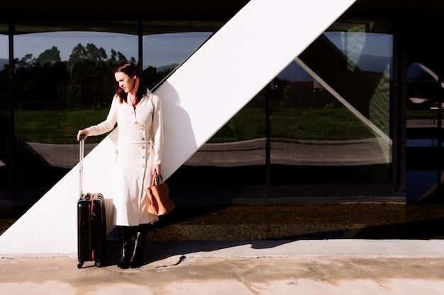 Bella giovane donna adulta in viaggio d'affari in attesa di trasporto nell'area dell'ufficio sulla strada